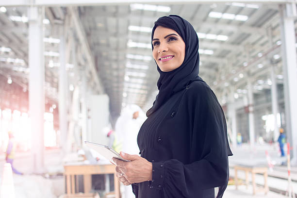 Confident Arab woman dressed in abaya looking forward while holding a digital tablet.